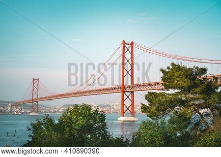 25 De April Bridge. Red Bridge Is Connecting Lisbon And Almada Across The River Tagus. Lisbon And Po