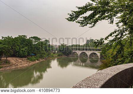 Guilin, China - May 11, 2010: Seven Star Park. Light Gray Stone Flower Bridge Over Greenish Xiadong