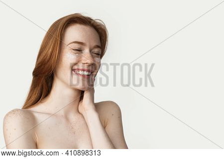 Ginger Woman With Freckles Is Applying Cream On Her Face Smiling On A White Wall With Bare Shoulders