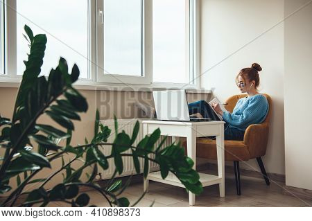 Caucasian Woman With Freckles And Red Hair Is Working At The Laptop While Wearing Hydrogel Eye Patch