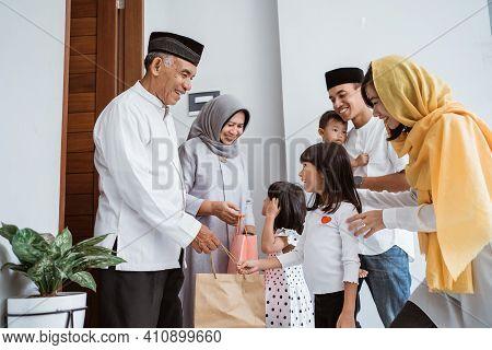 Family Giving Present To Their Muslim Grandparents During Eid Mubarak Celebration
