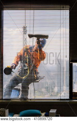 Bangkok, Thailand - December 1, 2015: A Daring Profession. A Window Cleaner Hanging On His Safety Ro