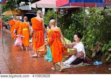 Luang Prabang, Laos - July 09, 2017: People In Luang Prabang, Lao  Make Merit By Giving Meal To Monk