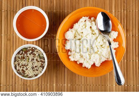 White Bowl With Liquid Honey, Bowl With Mix Of Different Seeds, Orange Glass Bowl With Cottage Chees