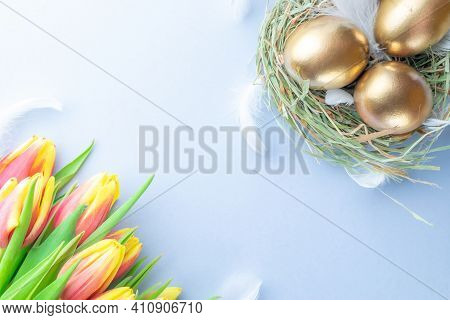 Easter Eggs Gold. Golden Colour Egg In Basket With Spring Tulips, White Feathers On Pastel Blue Back