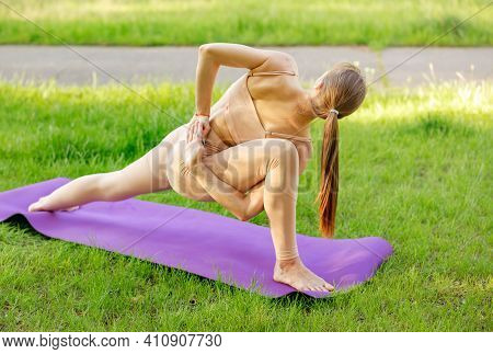 Flexible Woman Meditating. Trusting My Balance. Girl Doing Yoga On Yoga Mat In The Park. Unknown Wom