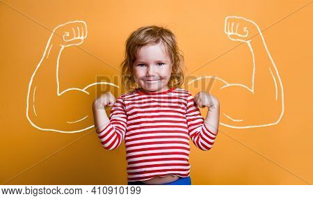 Funny Strong Child With Muscles Over Yellow Wall. Nerd Kindergarten Kid Girl Showing Bicep Muscles.