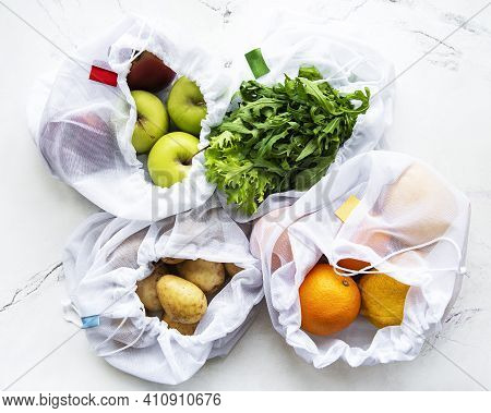 Fruits And Summer Vegetables In Reusable Eco Friendly Mesh Bags On Marble Background. Zero Waste Sho