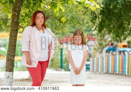 Family. A Distressed Mother And Daughter, Quarreling In The Park. The Concept Of Children's Whims An
