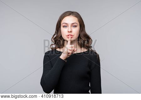 Dont Tell Anyone. Beautiful Serious Young Woman Holding Finger At Her Lips, Saying Shh, Hush, Demand