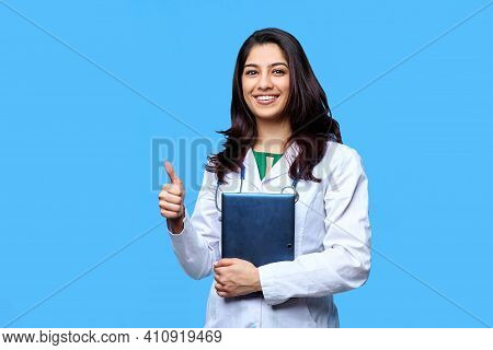 Beautiful Young Asian Girl Doctor, With A Laptop For Records Isolated On A Blue Background. Medical