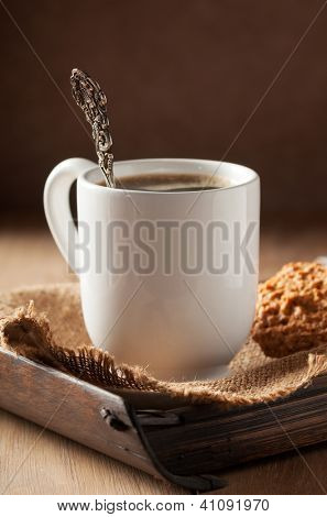 Antique coffee spoon in cup of coffee - focus on rim of cup and spoon