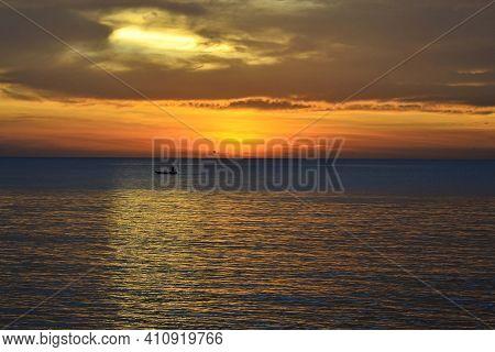 Evening Sunset At The Beach And Fisherman Fishing From Afar At Tanjung Aru Beach, Kota Kinabalu, Bor