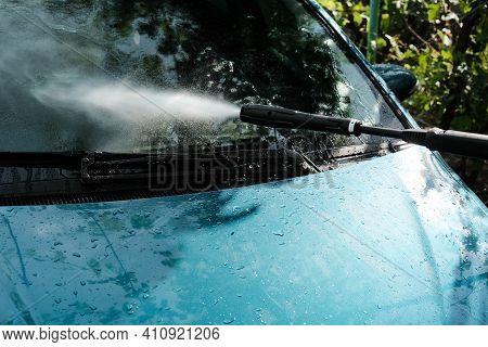 Car Wash At Home Alone. Car Wash High Pressure Close-up. A Man Washes A Green Car.