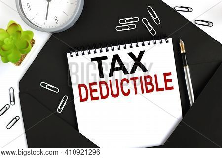 Tax Deductible. Text On A Sheet Of Notepad On A Black Envelope On A Light Background