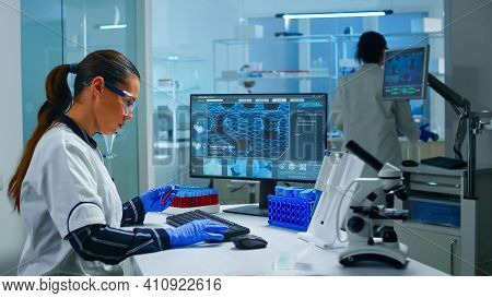 Chemist Doctor Holding Test Tube With Blood Sample Entering Datas In Pc Working In Lab. Team Of Scie