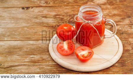 Glass Of Tomato Juice On Wooden Table. Fresh Tomato Juice And Chopped Tomatoes On Wooden Board