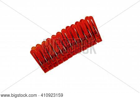 A Set Of New Brown Plastic Clothespins On A White Background. New Clothespins Folded Tightly Togethe