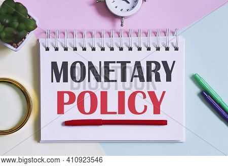 Monetary Policy Text Written On Notebook With Pencils, Magnifier