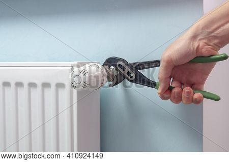 Plumber Fixing Radiator With Wrench. Heating Radiator With Temperature Regulator, Thermostat.