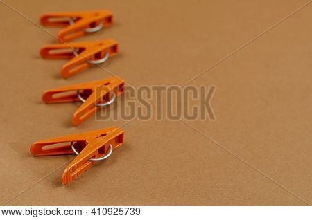 Brown Plastic Clothespins On A Brown Background. A Line Of New Clothespins. Side View At An Angle. S