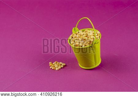 Dry Yellow Peas And Green Bucket On A Pink Background. A Full Metal Bucket Of Split Peas. Close-up,