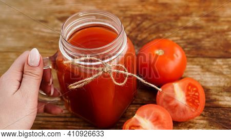 Female Hand Holds Glass Of Tomato Juice On Wooden Table. Fresh Tomato Juice And Chopped Tomatoes On