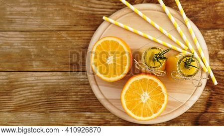 Orange Juice In Glass Bottles. The Juice Is Decorated With A Sprig Of Rosemary. Juice On Wooden Back