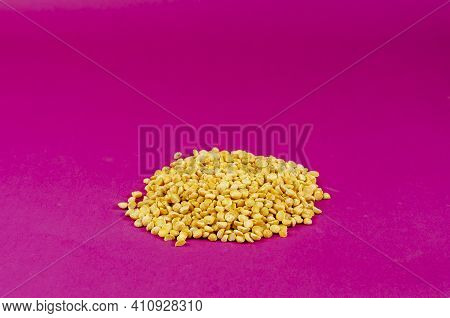 Dry Yellow Peas On A Pink Background. A Pile Of Split Peas. Close-up, Selective Focus