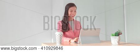 Working from home office Asian business woman using laptop for videocall or banking financial services wearing professional suit for live stream videoconference. Panoramic banner.