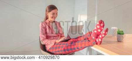 Working from home Asian woman streaming videoconference online in pajamas with suit blazer for remote work. Funny pandemic lifestyle concept panoramic banner.