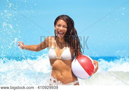 Happy beach Asian bikini woman having fun running in waves playing with beach ball on summer travel vacation. Holidays in caribbean destination.