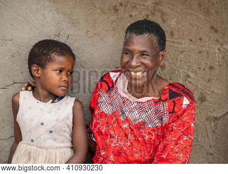 old African woman and her granddaughter sitting in her yard in a village in Botswana