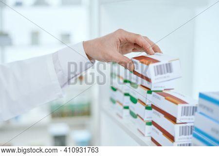 Image Of A Druggist Taking A Box Of Medicine.