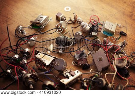 Electric guitar electronic parts, scattered on a old work bench. Guitar wiring components.