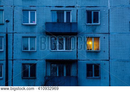 Wall of multi-storey residential building with Iluminated window. Detail of soviet era block apartment building