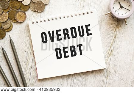 Overdue Debt Text On A Sheet Of Notepad. Coins Are Scattered, Pencils On A Gray Wooden Background.