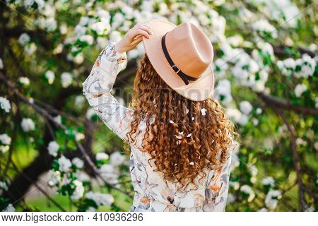 Backview Of A Young Woman With Blossom In Her Curly Hair Wearing Beige Hat And White Dress, Standing