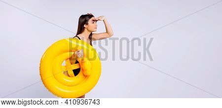 Banner, Long Format. A Young Girl Lifeguard Looks Into The Distance Holding A Yellow Lifebuoy In Her
