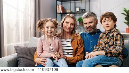 Portrait Of Cheerful Positive Caucasian Family Parents With Children Gathered Together At Home Sitti