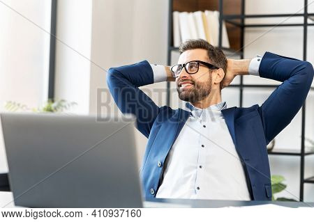 Smiling Man With Glasses Sitting At The Laptop, Holding Hands Behind Head, Relaxing, Looking At Good