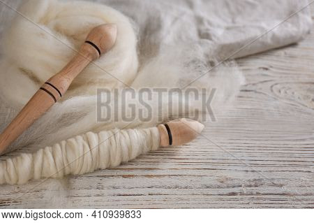 Soft Wool And Spindles On White Wooden Table, Closeup