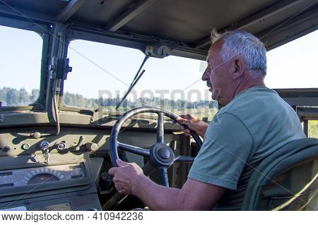 Moscow, Russia, 2018-08-25, A White-haired Man Driving A Very Old Military Vehicle. Military Vehicle