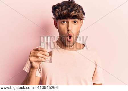 Young hispanic man drinking glass of water scared and amazed with open mouth for surprise, disbelief face