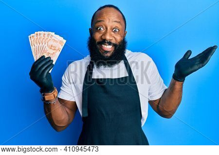 Young african american man wearing professional apron holding turkish liras banknotes celebrating achievement with happy smile and winner expression with raised hand