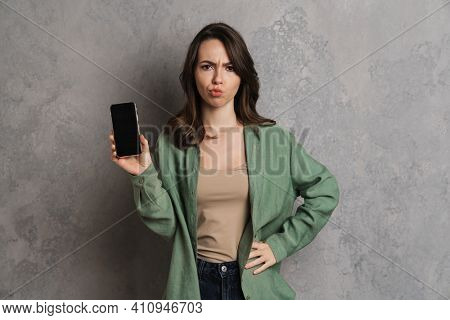 Displeased caucasian girl showing cellphone at camera isolated over grey wall