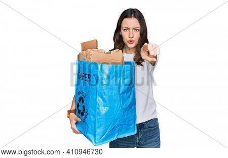 Young beautiful woman holding recycling wastebasket with paper and cardboard pointing with finger to the camera and to you, confident gesture looking serious