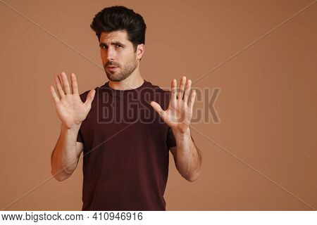 Displeased unshaven young man showing stop gesture at camera isolated over beige background