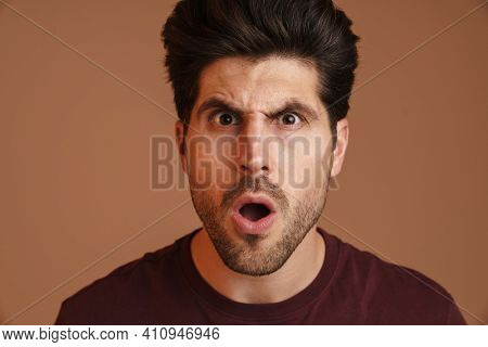Displeased unshaven young man expressing surprise on camera isolated over beige background