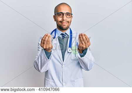 Hispanic adult man wearing doctor uniform and stethoscope doing money gesture with hands, asking for salary payment, millionaire business